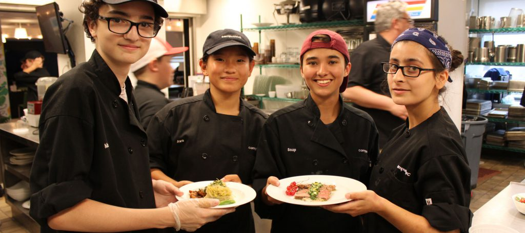 Happy student chefs creating and plating/
